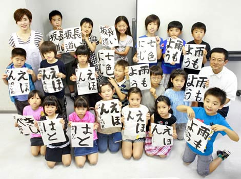 children at a calligraphy classroom smiling with their work in their hands cooperation with hakushu - Cool Pictures For Kids